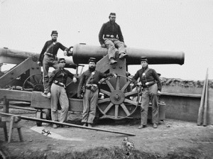 Civil War soldiers stand around a big gun - one sits on it