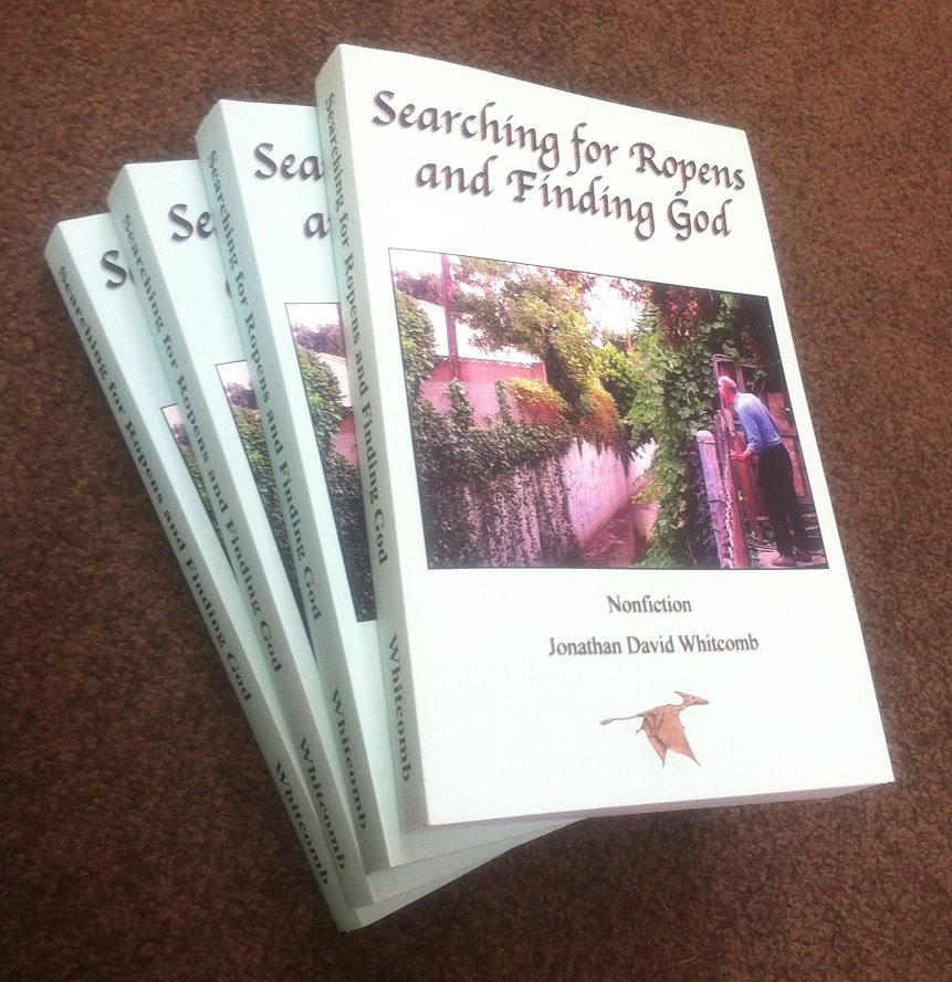 "small pile of books: ""Searching for Ropens and Finding God"" by Jonathan Whitcomb"